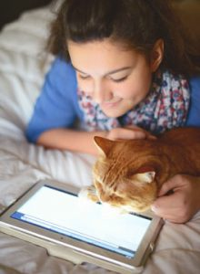 Girl and cat looking at tablet